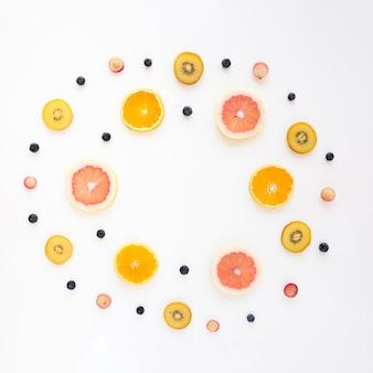 Cornice circolare realizzata con arancio; uva; kiwi; pompelmo e mirtilli su sfondo bianco