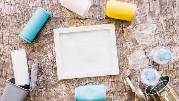 Cornice circondata da bottiglie di plastica, lattine e pattumiere