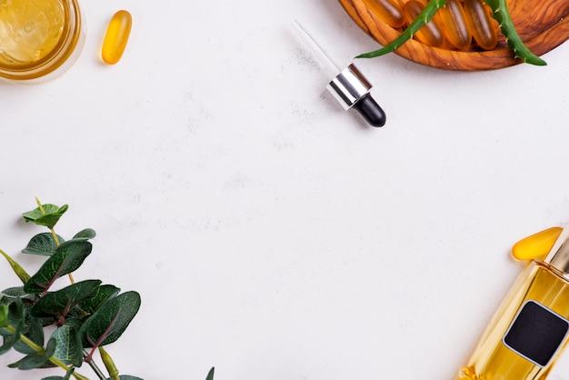 Cornice con crema cosmetica, capsule di gel omega 3 e siero in bottiglie di vetro su bianco