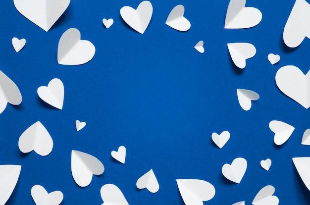 Cornice con cuori di carta bianca su sfondo blu, vista dall'alto. colore dell'anno 2020 blu classico. copia spazio ...