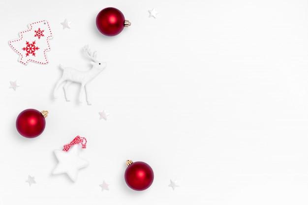 Cornice con palline rosse, stelle bianche, albero di natale, cervi su carta bianca