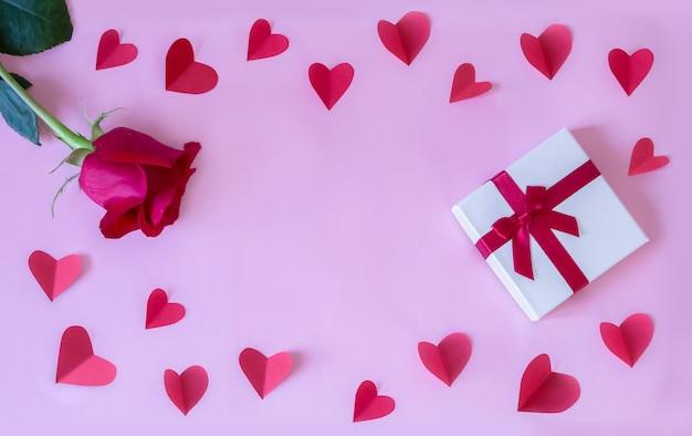 Cornice con rosa rossa fresca e confezione regalo e cuori di carta e sfondo di carta rosa