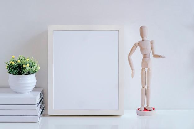 Cornice del modello con la bambola, il libro e la pianta da appartamento di legno sulla tavola bianca