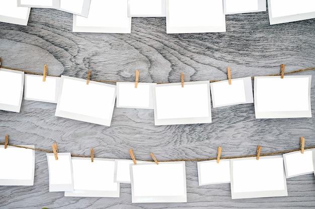 Cornice della carta in bianco che appende sulla corda da bucato su fondo di legno con il percorso di ritaglio.