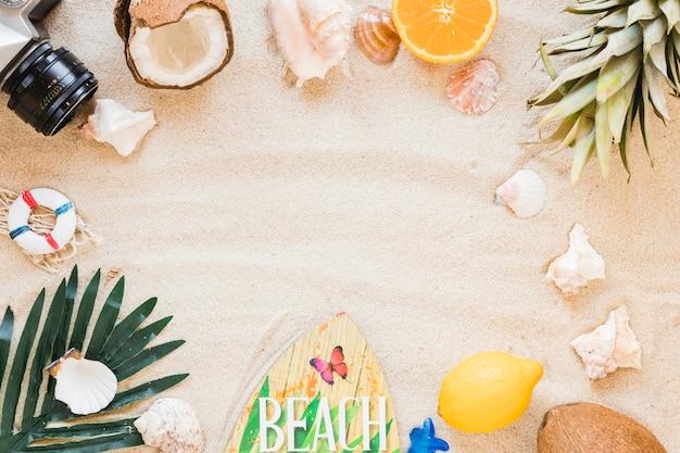Cornice della fotocamera, frutta esotica e tavola da surf sulla sabbia