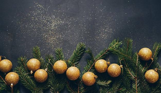 Cornice di abete verde e decorazioni natalizie su sfondo nero con spazio vuoto