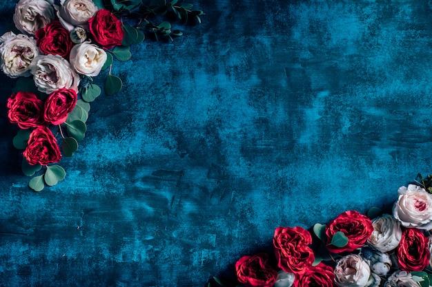 Cornice di bellissimi fiori con rose su sfondo blu