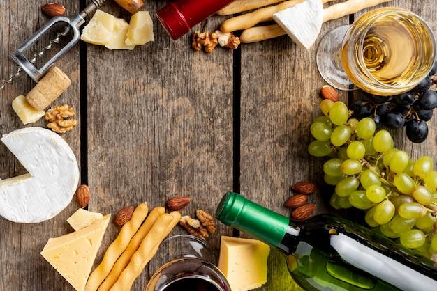 Cornice di bottiglia di vino, bicchiere e merenda