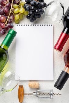 Cornice di bottiglie di vino con il taccuino