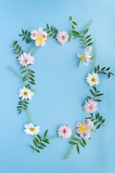 Cornice di camomille, rami, foglie e petali lilla su sfondo blu. vista piana, vista dall'alto