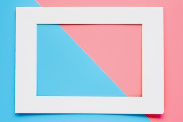 Cornice di carta bianca su sfondo di colore pastello rosa-blu