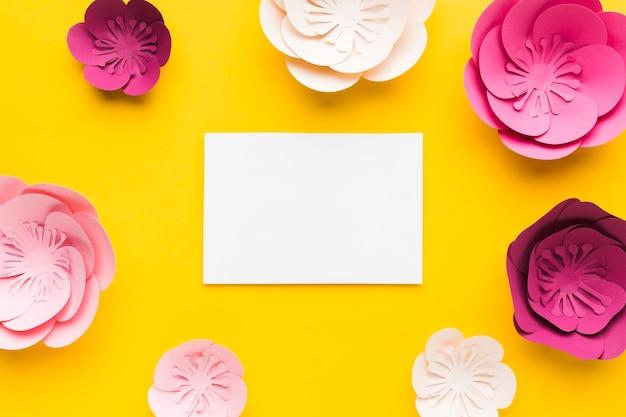 Cornice di carta floreale vista dall'alto con foglio di carta bianco
