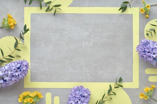Cornice di carta gialla con spazio testo decorato con fiori di giacinto blu e foglie di eucalipto