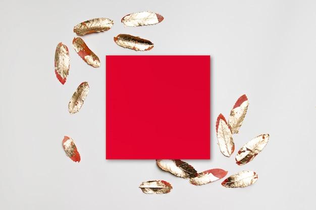 Cornice di carta rossa minima con foglie d'oro su uno sfondo grigio.