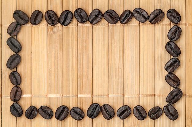 Cornice di chicchi di caffè su un tovagliolo di bambù