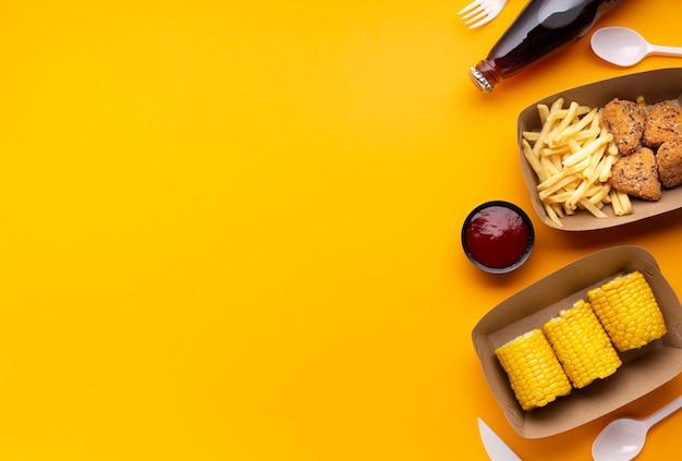 Cornice di cibo vista dall'alto con fast food e mais