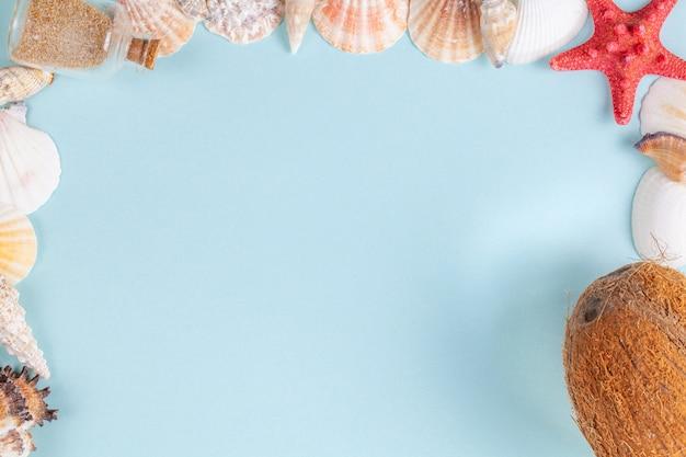 Cornice di conchiglie, bottiglia con sabbia e cocco su sfondo blu