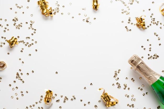 Cornice di coriandoli d'oro con bottiglia di champagne