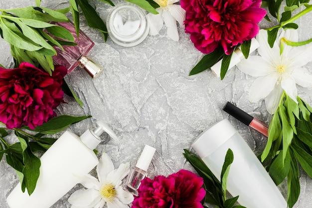 Cornice di cosmetici e profumi con fiori