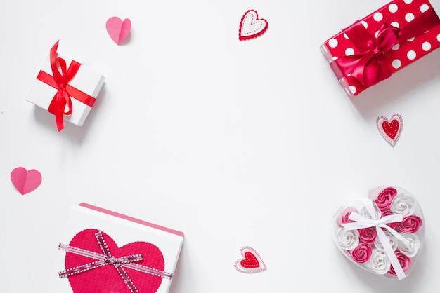 Cornice di decorazioni romantiche, regali, rose, cuori su uno sfondo bianco con spazio di copia.