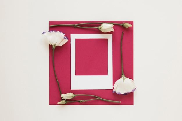 Cornice di fiori bianchi che circonda un pezzo di carta vuoto con cornice per foto