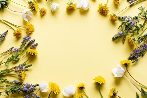 Cornice di fiori di campo su un tavolo giallo