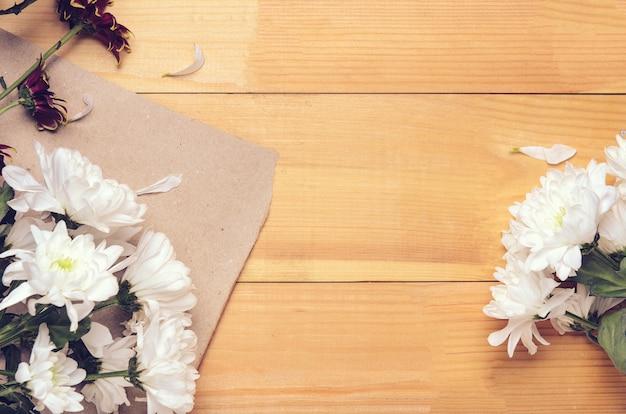 Cornice di fiori di crisantemo bianco e rosso su carta artigianale.