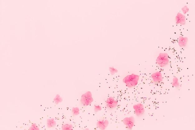 Cornice di fiori e coriandoli sparsi sul rosa.