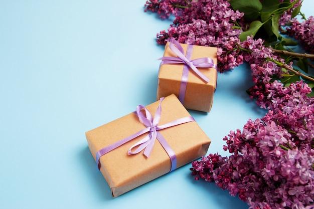 Cornice di fiori lilla con due scatole regalo su uno sfondo blu
