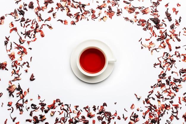 Cornice di foglie di tè carcade su un muro bianco con una tazza di tè al centro
