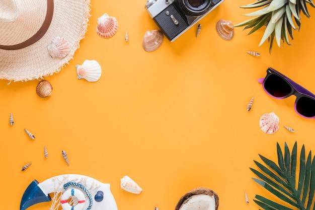 Cornice di fotocamera, conchiglie, cappello di paglia e frutta