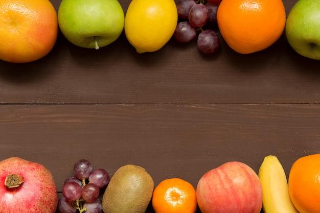Cornice di frutta con copia spazio sul tavolo in legno, cibo sano, dieta, giardinaggio o concetto vegetariano