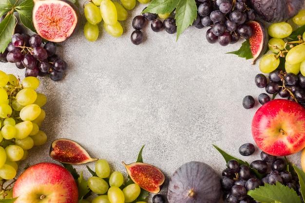 Cornice di frutti autunnali freschi. uva nera e verde, fichi e foglie su un tavolo grigio con copia spazio.