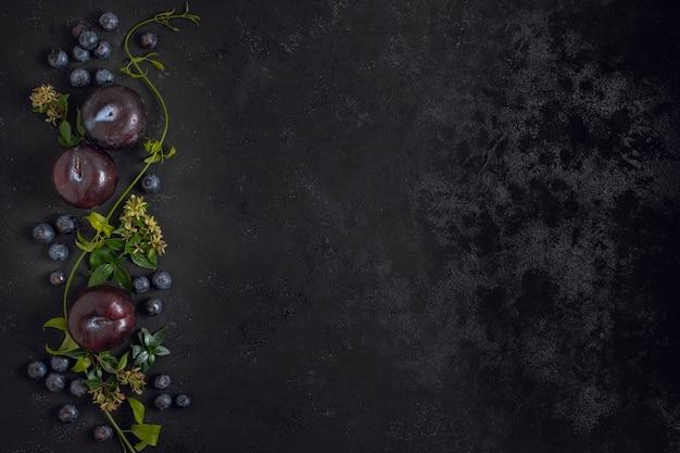 Cornice di frutti di prugna con spazio di copia