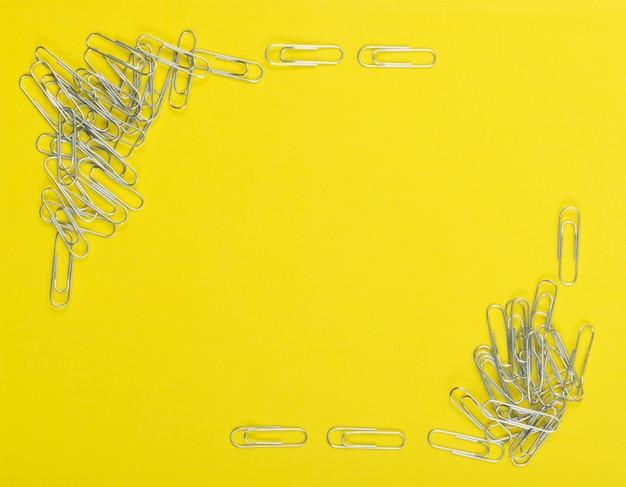 Cornice di graffette nota su sfondo giallo vista dall'alto. pila di clip in acciaio o graffette da vicino