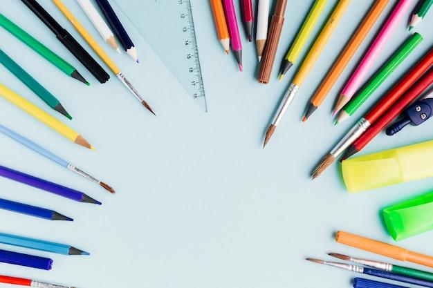 Cornice di matite colorate e pennelli