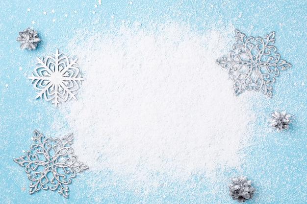 Cornice di natale azzurro di neve e fiocchi di neve d'argento.