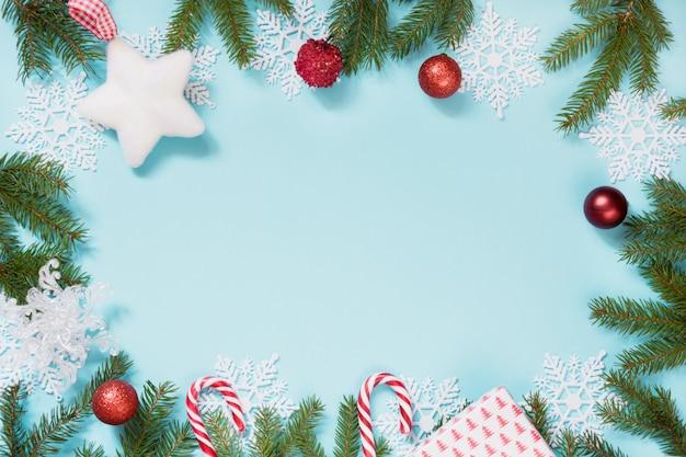 Cornice di natale con palline rosse, fiocchi di neve e rami su sfondo blu
