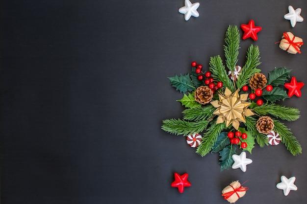 Cornice di natale con rami di abete, caramelle, regali e stelle d'oro sul buio