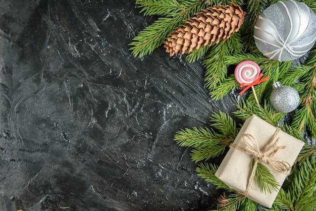 Cornice di natale con rami di abete, confezione regalo e pigne sulla superficie nera.