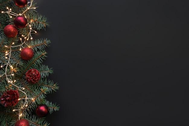 Cornice di natale con rami di abete, palle rosse, ghirlanda su sfondo nero. , vista da sopra, disteso.