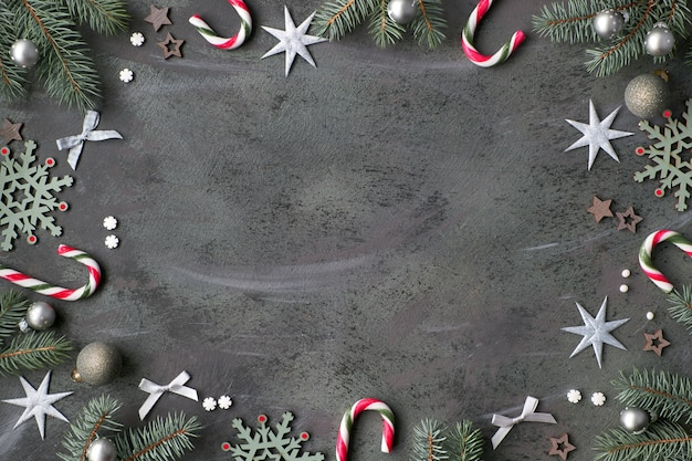 Cornice di natale con ramoscelli di abete, bigiotteria in verde, rosa e argento con stelle, bastoncini di zucchero, palline e fiocchi di neve