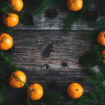 Cornice di natale di mandarini, rami di abete e coni
