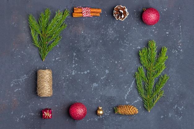 Cornice di natale di rami di abete, cono, cannella, corda e decorazione su uno sfondo scuro