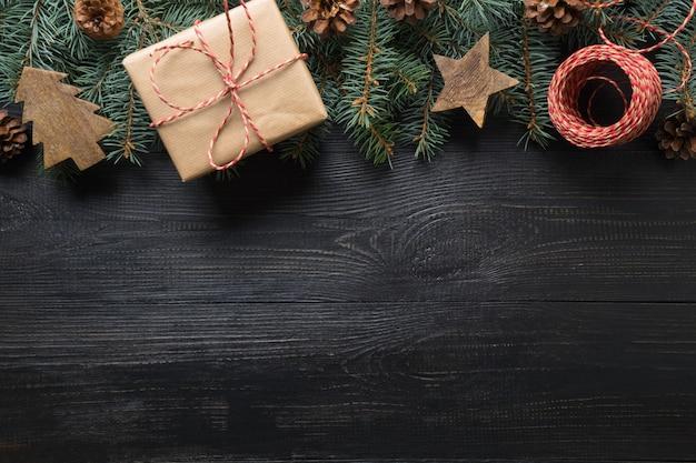 Cornice di natale di rami di abete, regalo artigianale e giocattoli di legno su tavola di legno scuro. vista dall'alto.