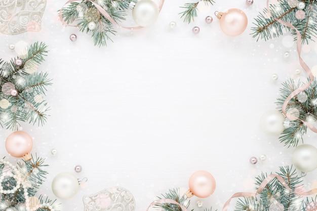 Cornice di natale di rami di abete verde, decorazioni e perle sulla superficie bianca