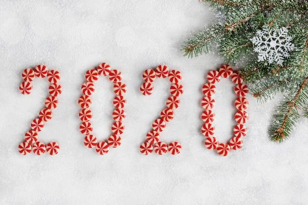 Cornice di natale e capodanno fatta di rami di abete, caramelle, fiocco di neve e decorazioni. carta da parati di natale. 2020 sfondo isolato su neve bianca. vista piana, vista dall'alto, copia spazio.
