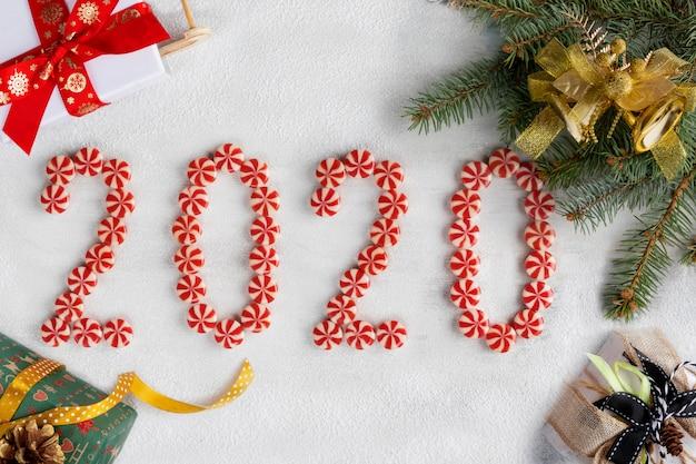 Cornice di natale e capodanno fatta di rami di abete, caramelle, regali e decorazioni. carta da parati di natale. 2020 sfondo isolato su neve bianca. vista piana, vista dall'alto, copia spazio.