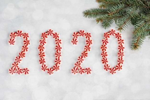 Cornice di natale e capodanno fatta di rami di abete e caramelle isolati su neve bianca. carta da parati di natale. 2020 sfondo sfocato. vista piana, vista dall'alto, copia spazio.