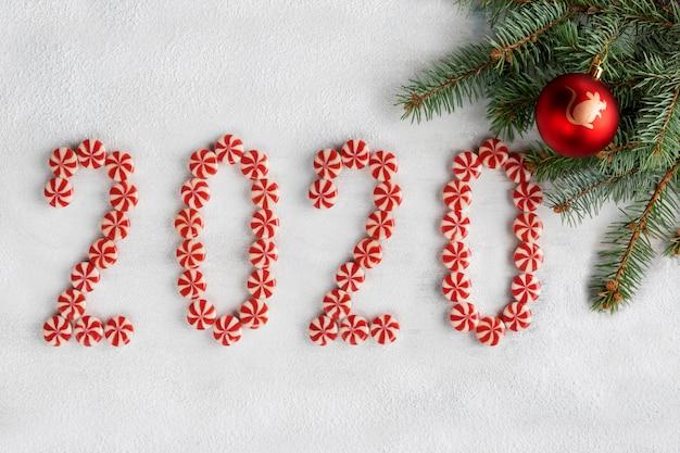 Cornice di natale fatta di rami di abete, caramelle, palla rossa con simbolo del nuovo anno e decorazioni. carta da parati di natale. 2020 sfondo isolato su neve bianca. vista piana, vista dall'alto, copia spazio.
